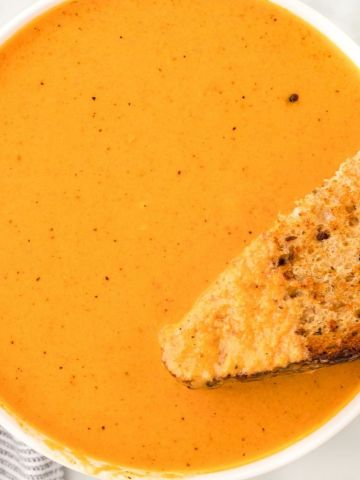 A white bowl with creamy tomato soup inside and a grilled cheese sandwich dipped into it.