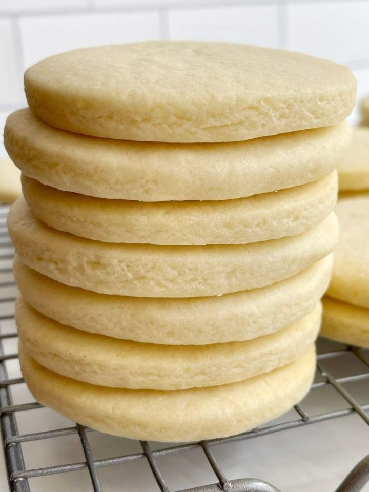 A stack of unfrosted sugar cookies on a cooling rack.