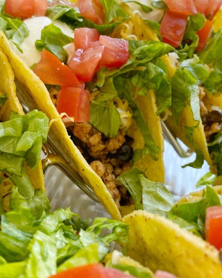 Green Chili Turkey Tacos with ground turkey, chopped onion, green chilies, black olives, and taco seasoning! A flavor explosion twist to traditional tacos. Top with lots of cheese and all your favorite taco toppings.