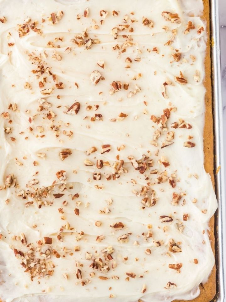 Overhead of pumpkin sheet cake topped with pecans.