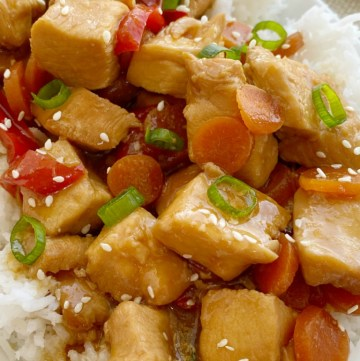 Mongolian Chicken is so easy to make in the slow cooker! Chunks of chicken that fall apart, red pepper, carrots cook in an easy homemade Mongolian inspired sauce. Serve over rice.