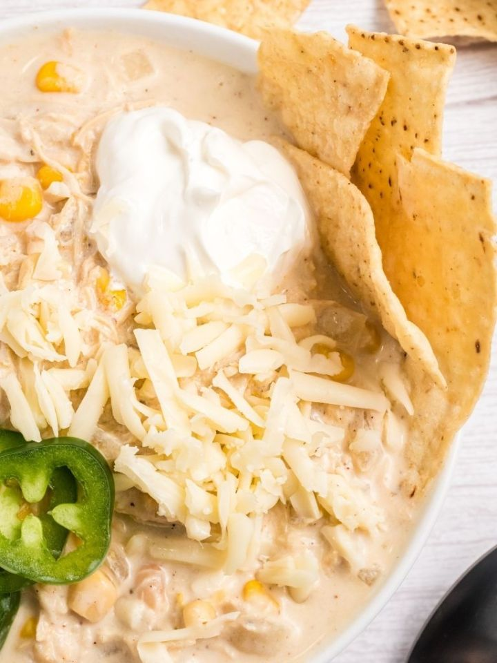 Bowl of white chicken chili with toppings.