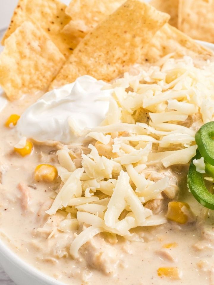 A close up shot of white chicken chili that's so creamy and topped with jalapeño slices, sour cream, chips, and shredded cheese.