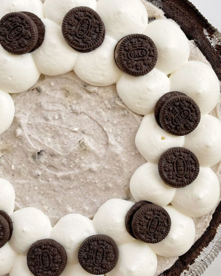 Oreo pudding pie garnished with whipped cream and Oreo cookies.
