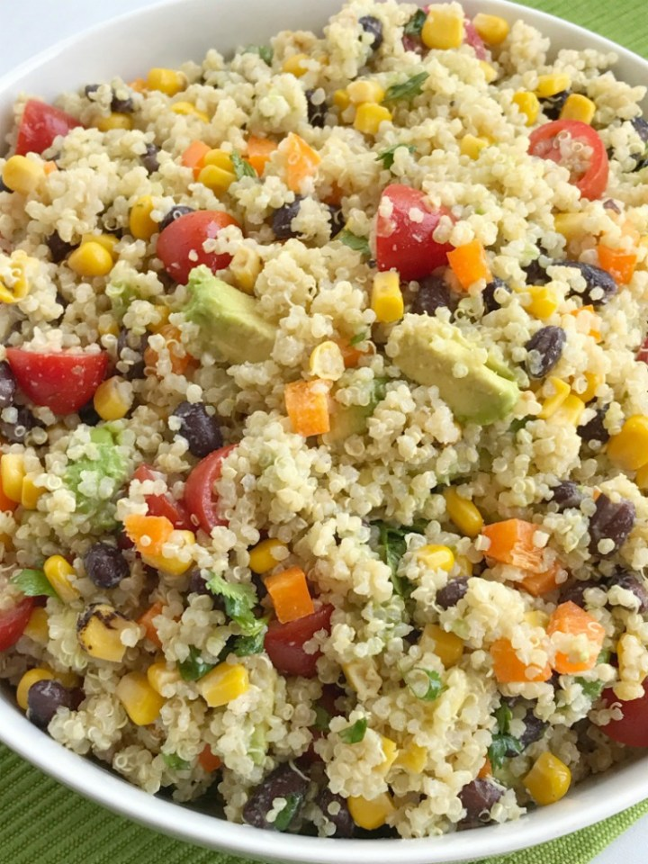 Fiesta quinoa salad is a healthy side dish or a delicious light lunch. Loaded with quinoa, beans, corn, tomatoes, sweet orange pepper, avocado and covered in a creamy cilantro lime vinaigrette dressing!