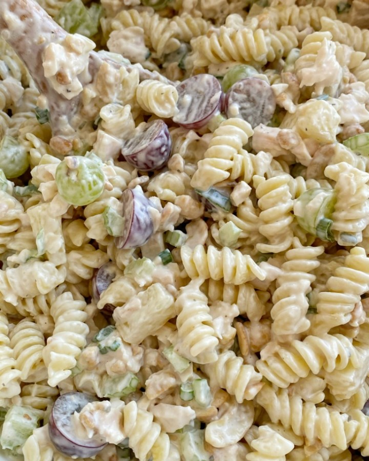 Cashew Chicken Pasta Salad is a creamy pasta salad recipe that's full of texture and flavor. Grapes, pineapple tidbits, celery, green onion, cashews, and chicken in a creamy ranch dressing sauce and spiral pasta noodles.