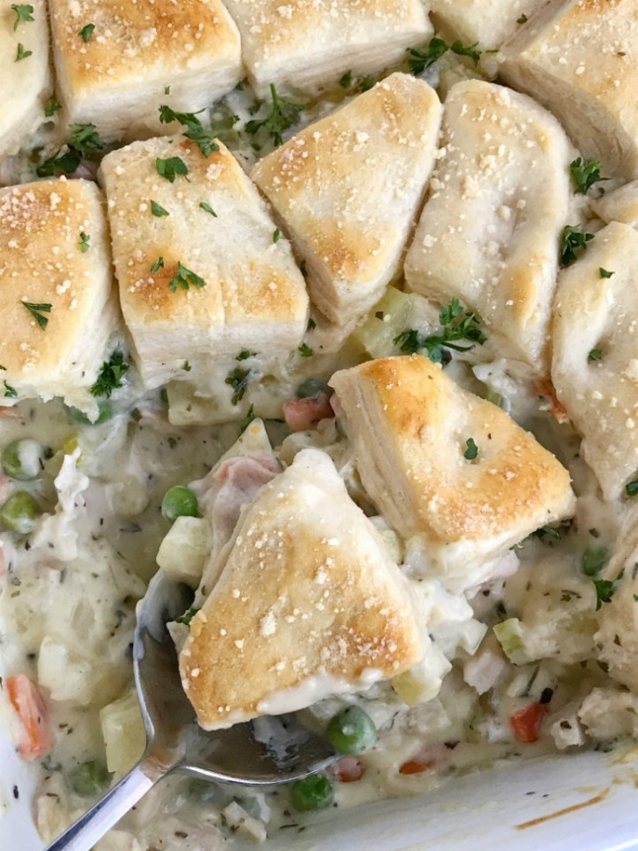 Creamy chicken pot pie casserole is the ultimate comfort food recipe. Vegetables and chicken simmer in a creamy chicken broth and then they're topped with flaky buttermilk biscuits. Creamy, warm, comforting, homemade goodness in one casserole pan | www.togetherasfamily.com #casserolerecipes #recipe #dinnerrecipes #chickenrecipes #chickencasserole #chicken #comfortfood