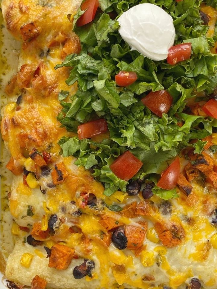 Sweet Potato Black Bean Enchiladas in one pan topped with green chili sauce and shredded lettuce, tomatoes, and sour cream.
