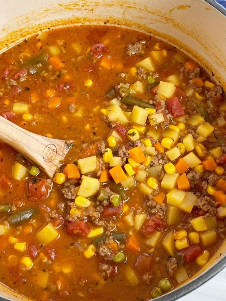 A pot of hamburger soup with a wooden spoon inside it.