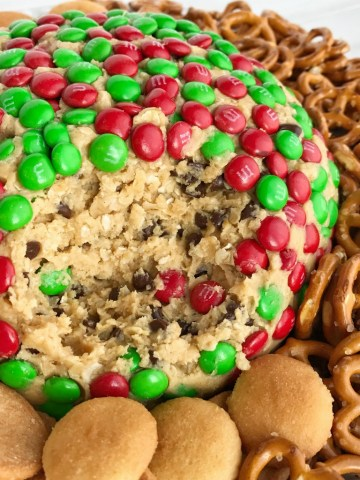 Christmas Cookie Dough Cheeseball Dip   Cookie dough cheeseball dip is the best appetizer or snack to take to a party or munch on during the Holidays! Red and green m&m's cover the outside of a peanut butter oatmeal chocolate chip cookie dough cheese ball. No flour and no eggs so it's perfectly safe to eat. Serve with pretzels, wafers, cookies, and anything else   www.togetherasfamily.com #christmascookies #appetizerrecipes