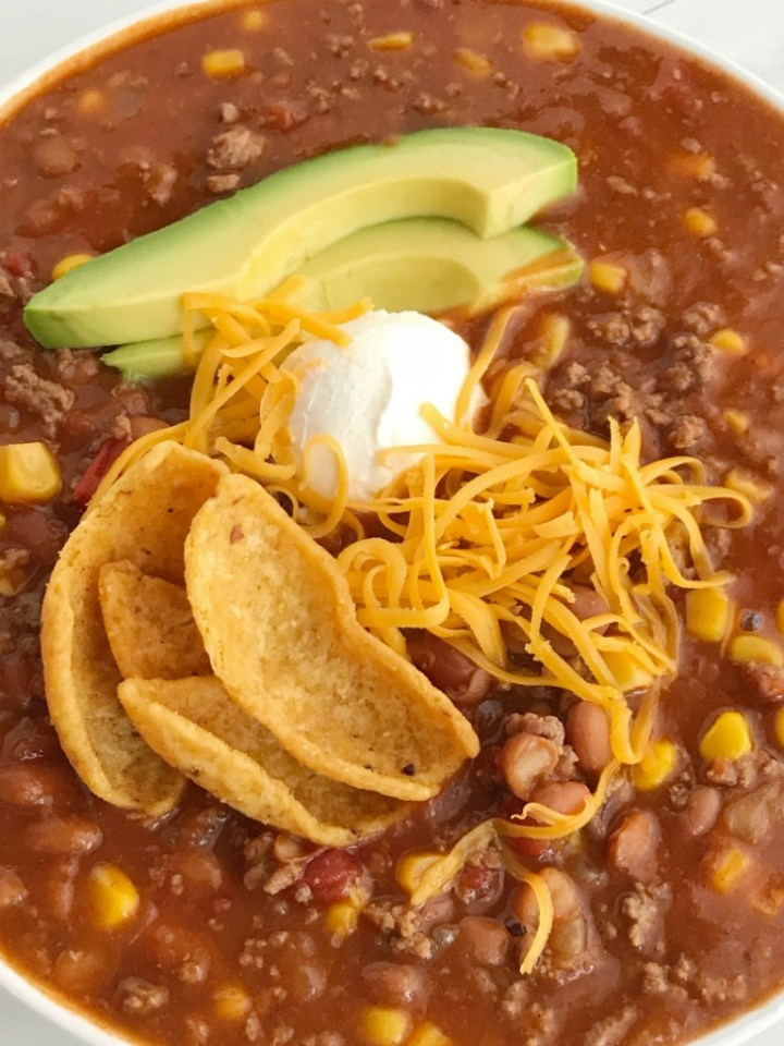Easy Taco Soup | Easy taco soup is loaded with ground beef, chili beans, corn, and tomatoes. Pile it high with corn chips, sour cream, and shredded cheese. Taco soup is a simple recipe that is so comforting during the cold winter months. One pot and about 30 minutes is all you need for an easy dinner! | Together as Family #tacosoup #tacosouprecipes #souprecipes #easyrecipes