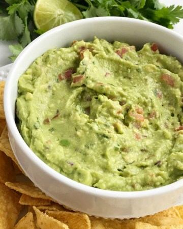 Salsa verde guacamole is loaded with tomato, cilantro, smashed avocado, jalapeno and salsa verde. Serve with tortilla chips for a delicious appetizer and a fan favorite for a game day party | Together as Family #guacamole #superbowlrecipes #appetizerrecipes #salsaverde #salsaverderecipes #healthyrecipes #recipeoftheday