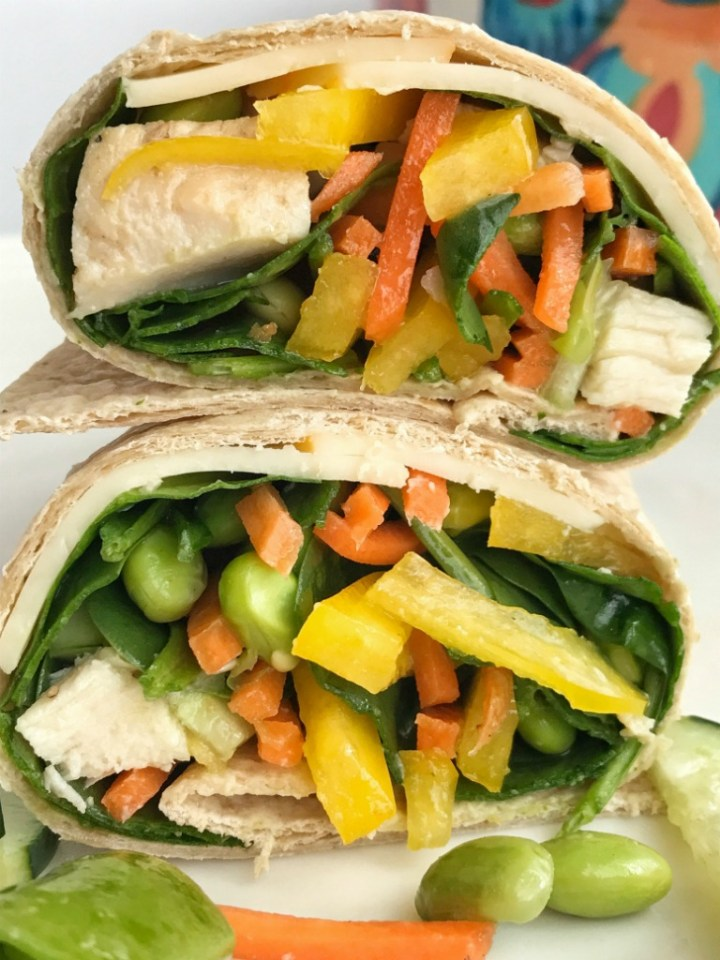 Sesame chicken vegetable wraps are a smart and healthy choice for lunch or dinner! Whole wheat tortilla filled with spinach, bell pepper, edamame, snap peas, cucumber, carrots, and chunked chicken and drizzled with a sesame citrus dressing   Together as Family #healthyfood #healthyrecipes #wraps #wraprecipes