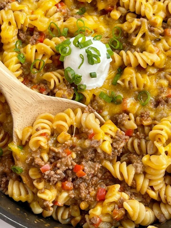 One pan bbq pasta skillet with ground beef shown in a pan with a wooden spoon taking a scoop out of it.