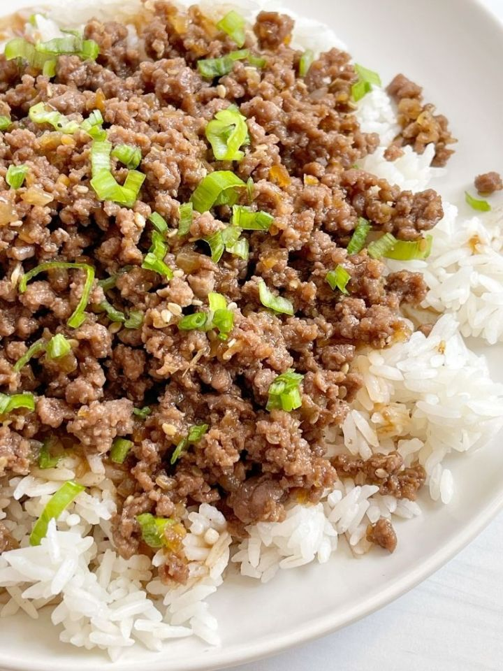 A white plate of white rice and ground beef teriyaki. Garnished with green onions.