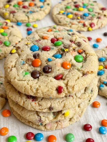 A stack of m&m cookies on a cookie sheet with mini m&m's around it.