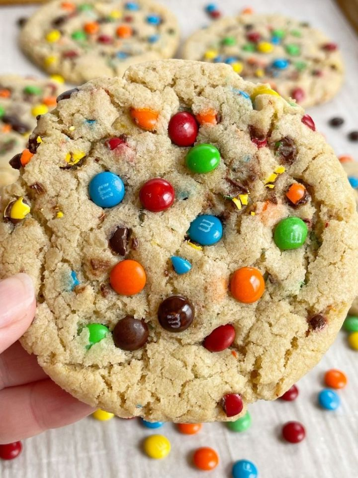 A hand holding a m&m cookie topped with mini m&m's on top.