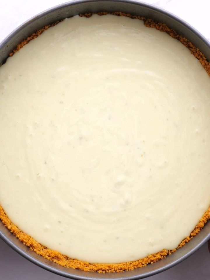 A springform pan with cheesecake mixture poured into it.