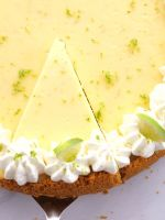 An overhead shot of key lime cheesecake with whipped cream garnish.