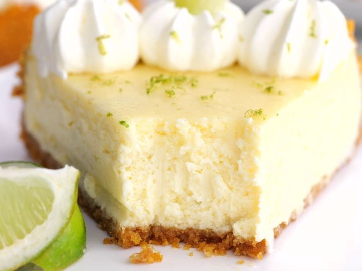 Horizontal photo of key lime cheesecake with a lime wedge next to it.