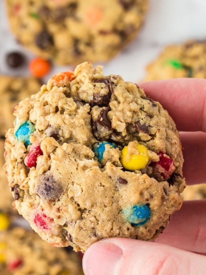 A hand holding one monster cookie in it with some cookies in the background.