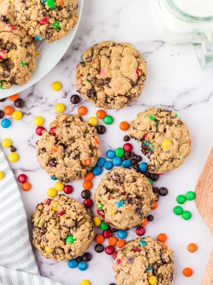 Overhead shot of monster cookies on a marble background with a glass of milk in the corner.