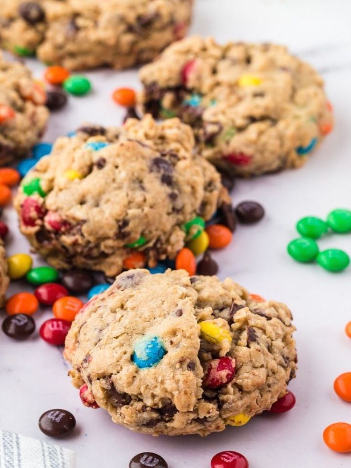 Monster cookies on a marble background, close up shot of one cookie, with m&m's beside it.