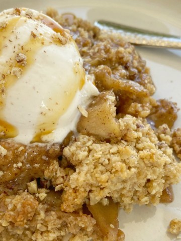 Apple Crumble with a delicious buttery oatmeal cookie crumble. Tart apples in cinnamon & sugar and butter topped with an easy oatmeal cookie mix crumble topping. As it bakes it creates this buttery brown sugar syrup! Serve with vanilla ice cream for the best apple crumble dessert ever.