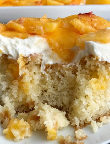 Peaches and Cream Poke Cake | Poke Cake Recipe | Cake | Dessert | If you love poke cakes then you must try this peaches and cream poke cake! French vanilla cake soaked in fresh peaches, frosted with a light and fluffy cream cheese whipped topping, and topped with chunked fresh peaches. #pokecake #cake #dessertrecipes #easydessertrecipe #peaches #peachrecipes