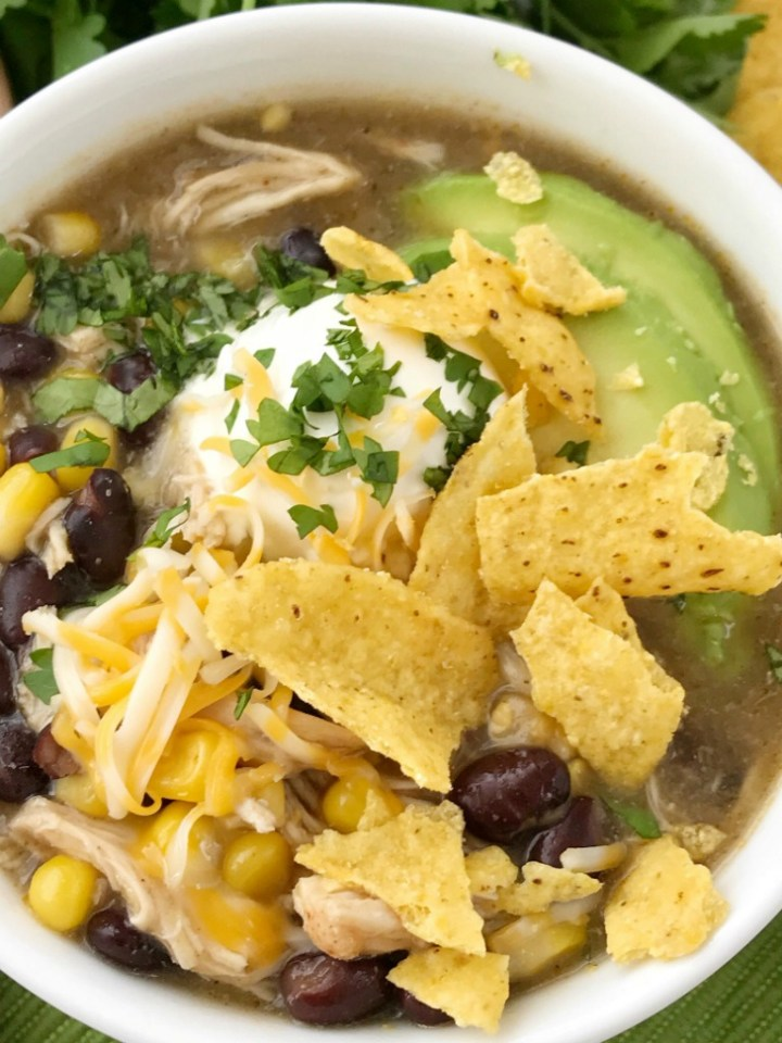 Chicken Enchilada Soup | Soup Recipe | Chicken Recipe | Chicken enchilada soup made in the slow cooker. Loaded with chicken, black beans, corn, that simmers in a green chili enchilada sauce and chicken broth in the crock pot. Serve with avocado, sour cream, cheese, and chips!