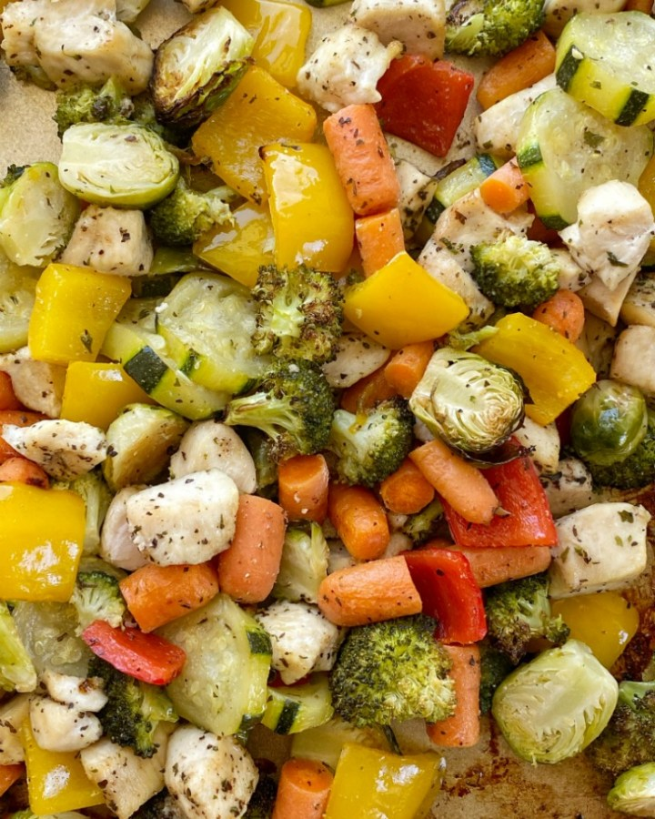 Baked Chicken and Vegetables roast in the oven on one sheet pan! Chicken breasts, bell peppers, Brussels sprouts, broccoli, carrots, and zucchini bake in seasoned olive oil.