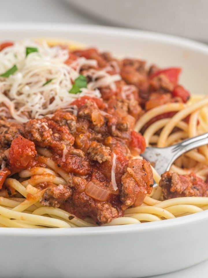 A plate of spaghetti with a fork twisting up spaghetti in it.