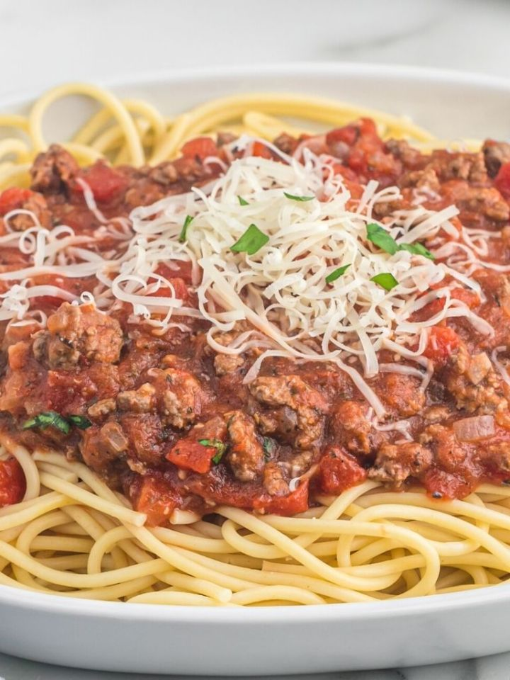 A white plate of spaghetti with meat sauce and parmesan cheese on top.