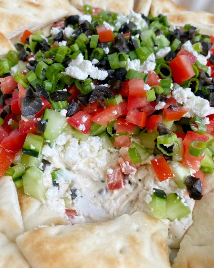 Greek Dip Recipe | Dip Recipe | Party Dips | Appetizer Recipe | This Greek inspired party dip is the best Dip Recipe you will make! Layers of cream cheese, yogurt, spices, tomatoes, cucumbers, olives, and feta cheese. Serve with crackers and pita bread for an amazing appetizer. #diprecipes #appetizers #superbowlrecipes #greekdip #recipeoftheday