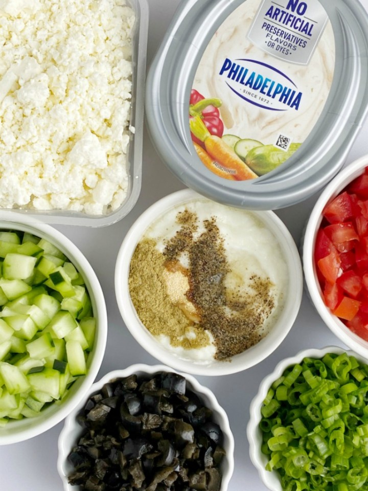 Greek Dip Recipe   Dip Recipe   Party Dips   Appetizer Recipe   This Greek inspired party dip is the best Dip Recipe you will make! Layers of cream cheese, yogurt, spices, tomatoes, cucumbers, olives, and feta cheese. Serve with crackers and pita bread for an amazing appetizer. #diprecipes #appetizers #superbowlrecipes #greekdip #recipeoftheday