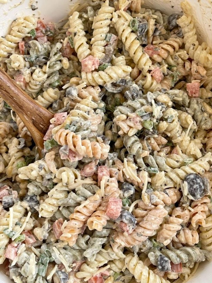 A bowl of pasta salad with a wooden spoon in it ready to serve.
