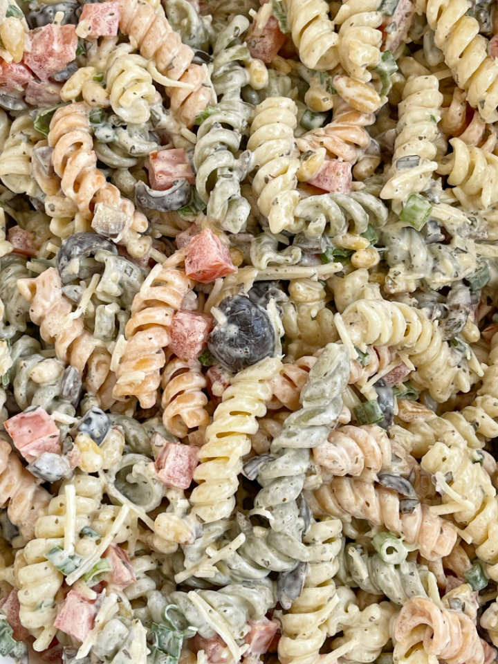 Close up picture of pesto pasta salad inside a white bowl.