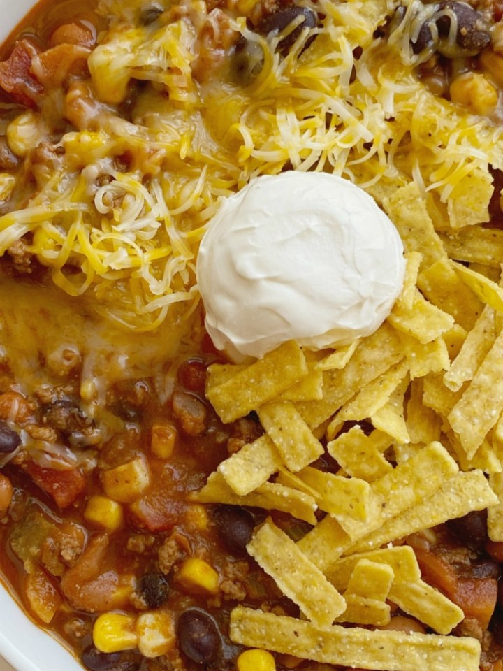 Taco Chili cooks in one pot on the stove! Ground beef, veggies, beans, and tomatoes simmer in a seasoned beef broth tomato base. The secret ingredient of cocoa powder makes this chili the best! Top with tortilla chips, sour cream, and cheese.