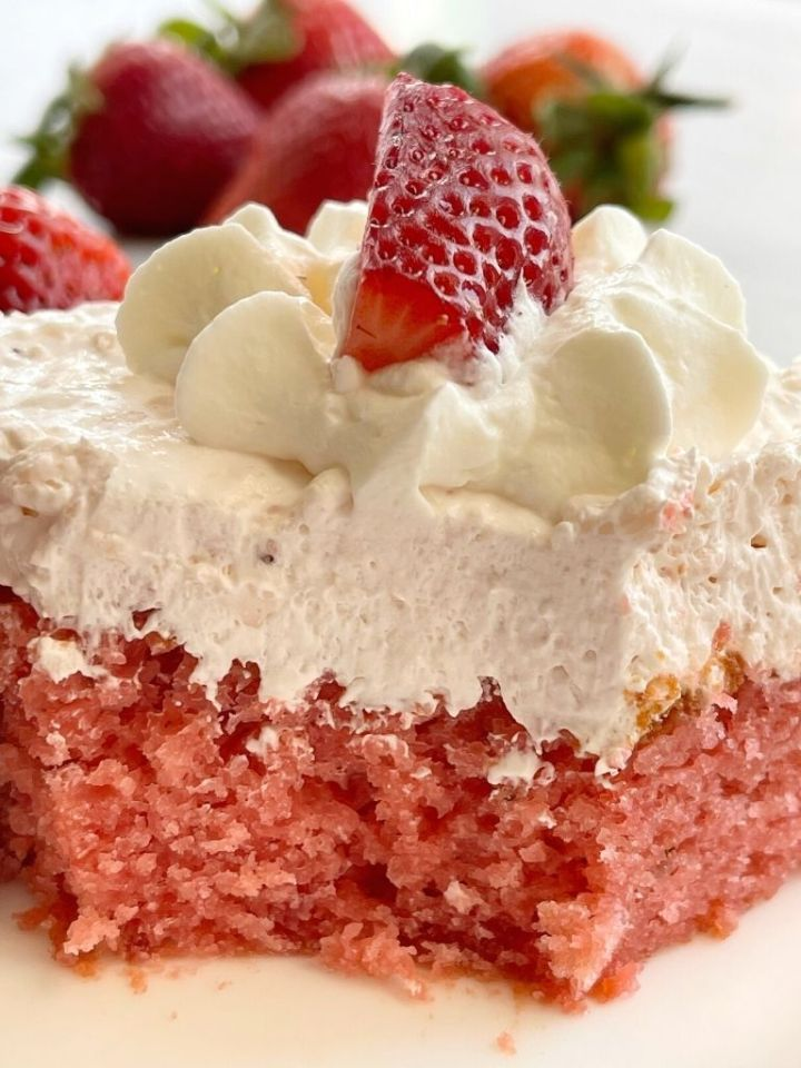 Strawberry cake on a plate with a bite taken out of it to show the moist texture of the cake.