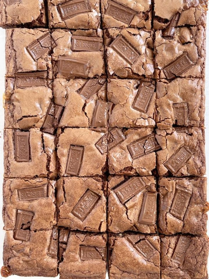 An overhead shot of a pan of brownies with Hershey chocolate bars on top. Cut into squares.