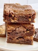 Stacked pile of cut brownies on a white plate.