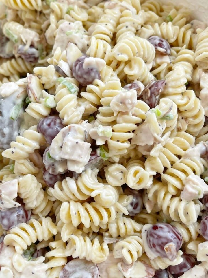 Poppy seed pasta salad inside a bowl with a wooden spoon.