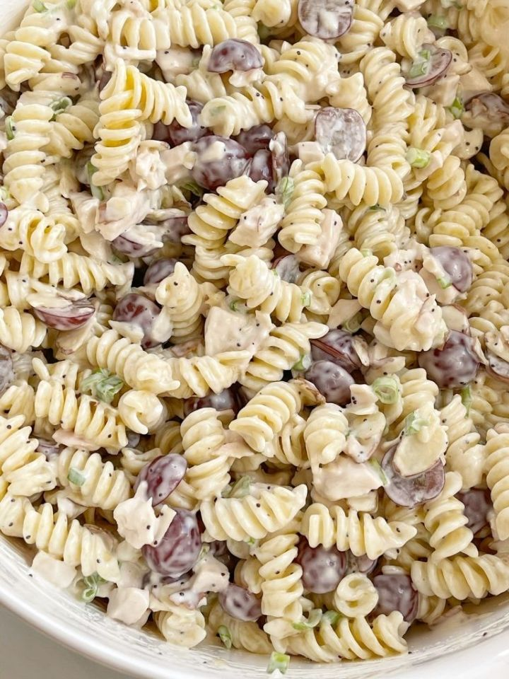 A bowl with chicken pasta salad in it, with grapes, almonds, and poppyseed dressing.