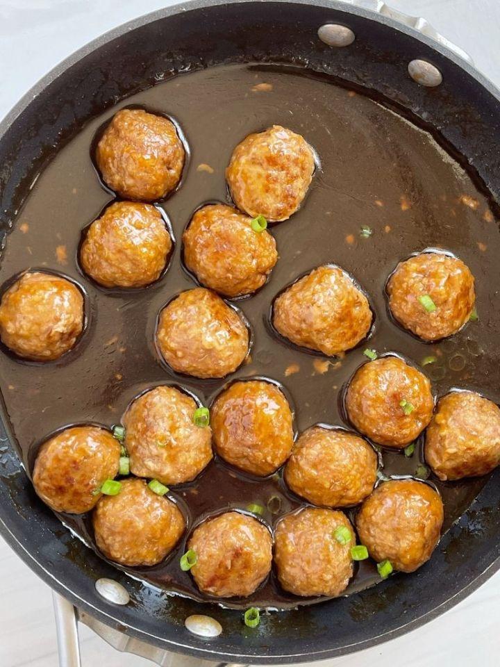 Meatballs in sauce inside a skillet pan.