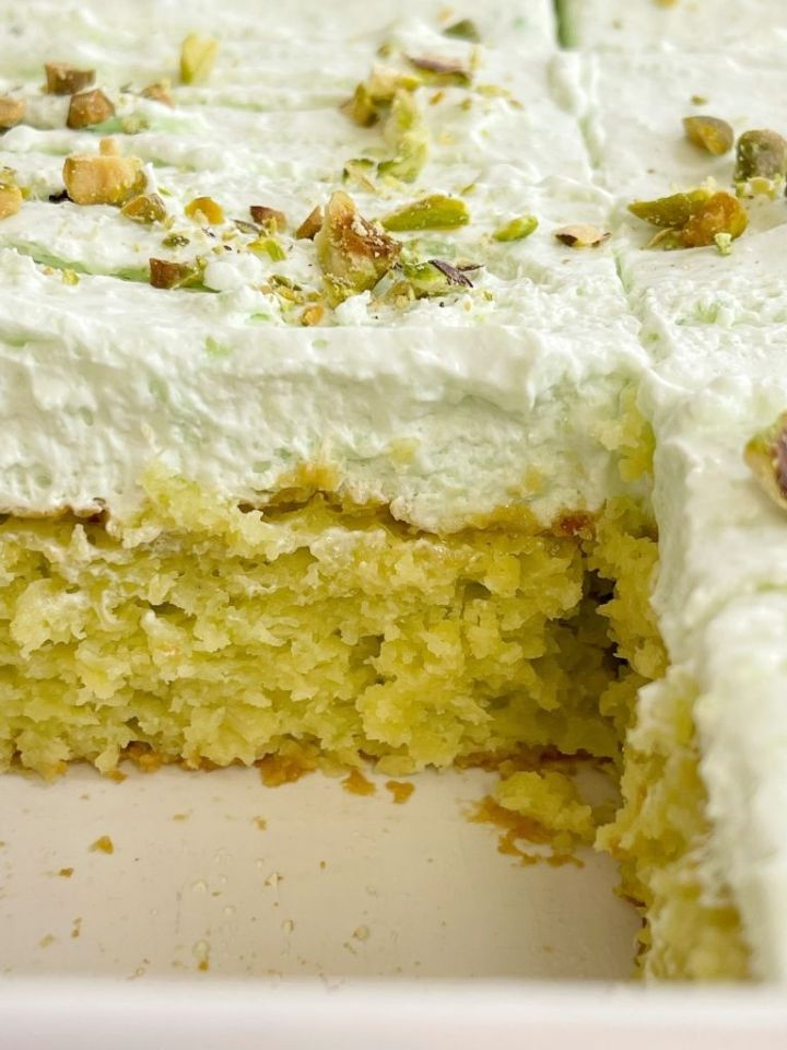 Pistachio cake inside a white pan topped with pistachio pudding frosting.