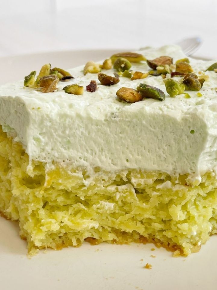 Slice of pistachio cake on a white plate.
