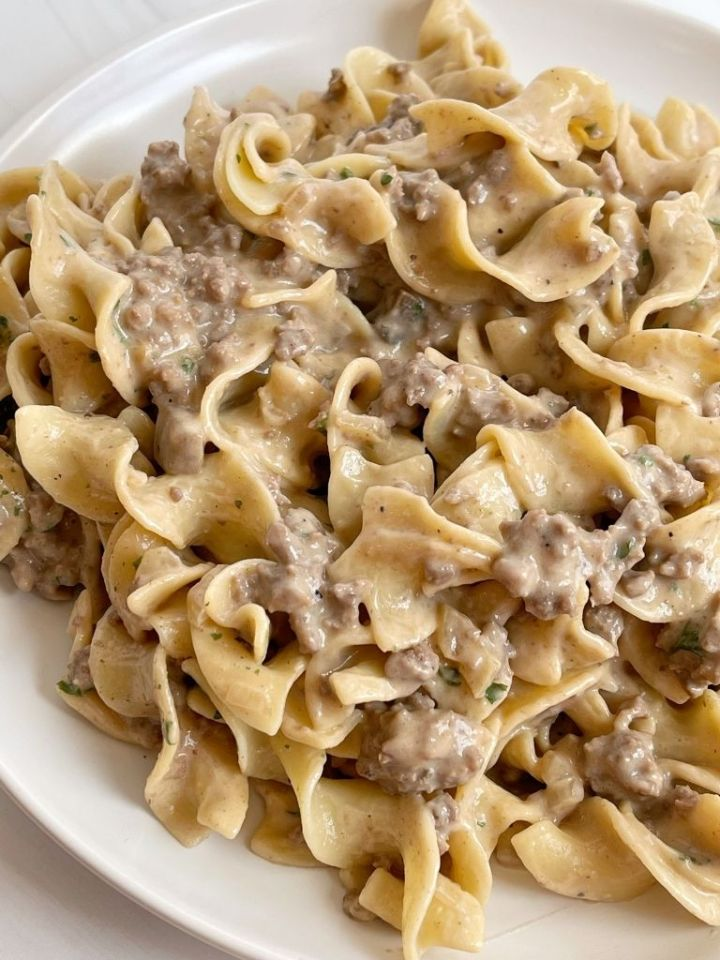 A white plate with beef stroganoff and egg noodles on it.