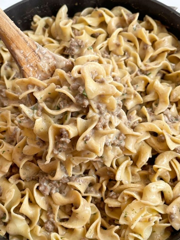A scoop of beef stroganoff on a wooden spoon inside a skillet pan.