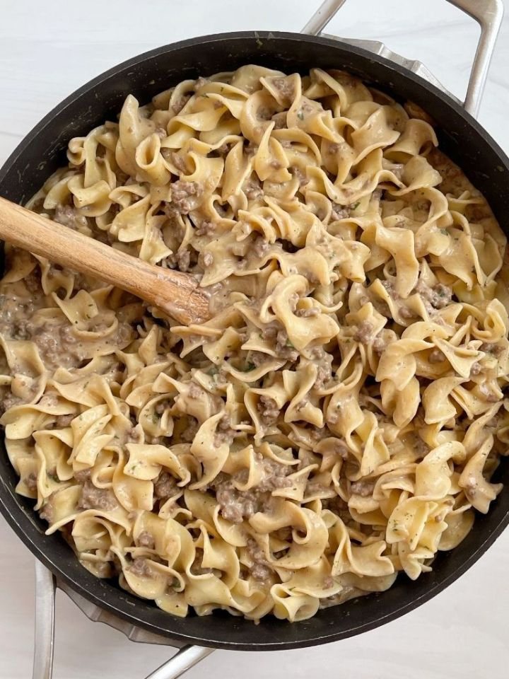 A picture of beef stroganoff with a wooden spoon inside the skillet pan.