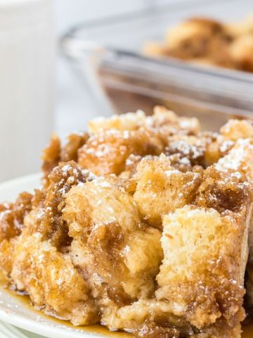 A serving of French toast casserole on top of a white plate with syrup on top.